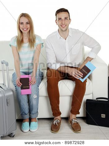 Portrait of young happy couple with baggage, sitting on sofa. Isolated on white