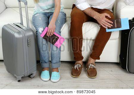 Legs of young happy couple with baggage and tickets, sitting on sofa