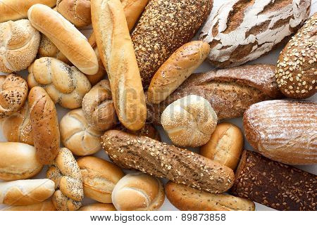 Many bread and rolls on wood, from above.