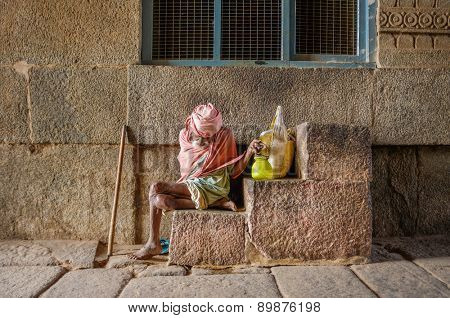 HAMPI, INDIA - 28 JANUARY 2015: Elderly Indian man begging in Virupaksha Temple which is part of Group of Monuments at Hampi, designated a UNESCO World Heritage Site.