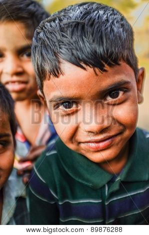 HAMPI, INDIA - 31 JANUARY 2015: Portrait of Indian boy with friends in background