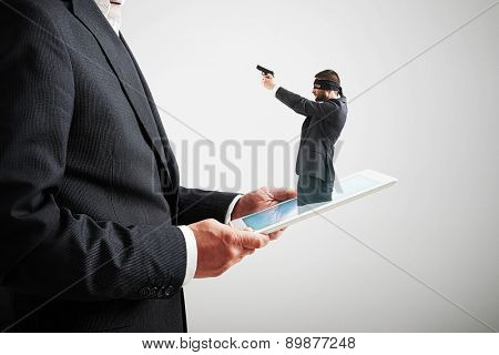 small man in mask and with gun got out of the tablet pc, and aiming at the big man over light grey background. cybercrime concept