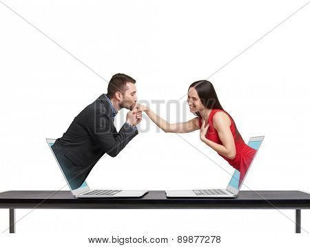 concept of love in social network. young man got out of the computer and kissing hand of beautiful young woman who got out of another computer over white background