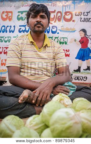 KAMALAPURAM, INDIA - 02 FEBRUARY 2015: Indian middle-aged man selling vegetables on a market close to Hampi