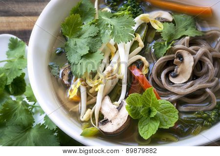 Hot and sour vegetable soup with soba noodles and bean sprouts.  Garnished with mint and coriander or cilantro.