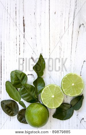 Kaffir lime leaves and cut and whole fruit, over distressed white timber.  Overhead view.