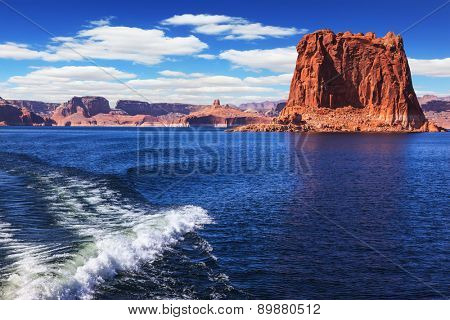 Foamy trace of a motor boat crosses the emerald waters. In the distance the coast of red sandstone. Lake Powell on the Colorado River