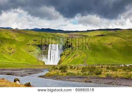 Huge picturesque waterfall and creek running along the road. Iceland, waterfall Skogafoll