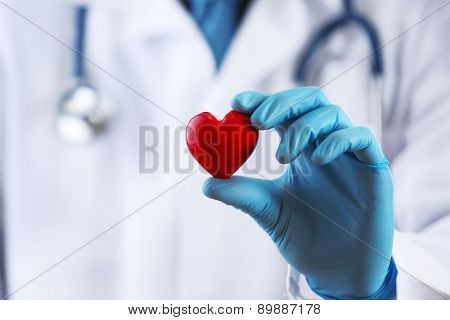 Doctor with stethoscope and small heart in hand, macro view