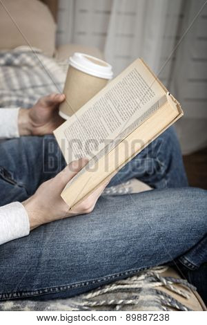 Young man reading book, close-up, on home interior background
