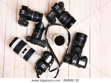 Modern cameras and cup of coffee on wooden table, top view