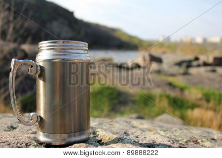 Thermos travel cup on nature background
