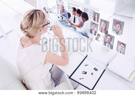 Female photo editor working on computer against group of business people brainstorming together