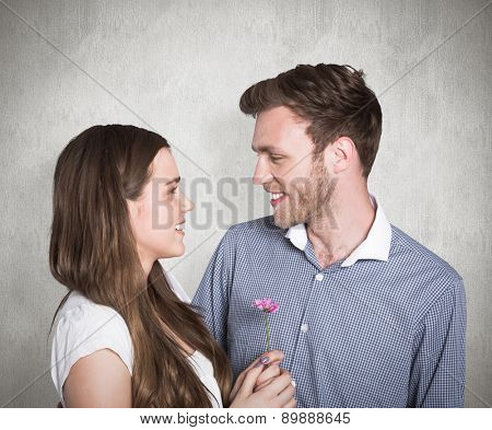 Man kissing woman as she holds flower against weathered surface