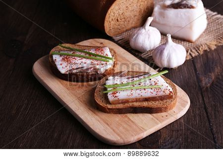 Sandwiches with lard on cutting board and garlic on wooden background