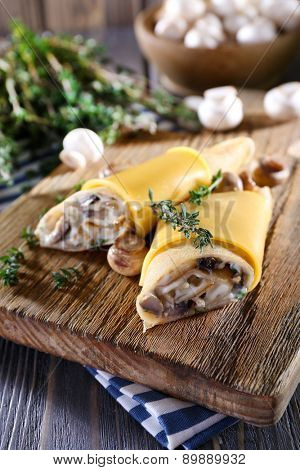 Pancakes with creamy mushrooms on wooden cutting board, closeup