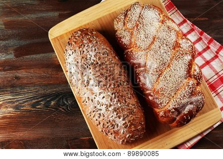 Fresh bread with bun on cutting board on table close up