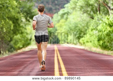 Male runner running on road training for fitness. Man doing jogging workout run outside in summer in nature. Athlete in running shoes and shorts working out for marathon.