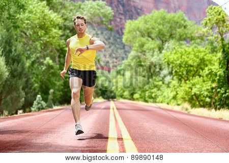 Running man sprinting looking at heart rate monitor smartwatch on run. Man jogging outside looking at his sports smart watch during workout training for marathon. Fit male fitness model in his 20s.