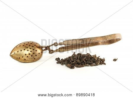 Heap of dry tea and old tea strainer isolated on white background
