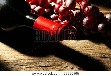 Glass bottle of wine with corks and grapes in dark with light on wooden table background
