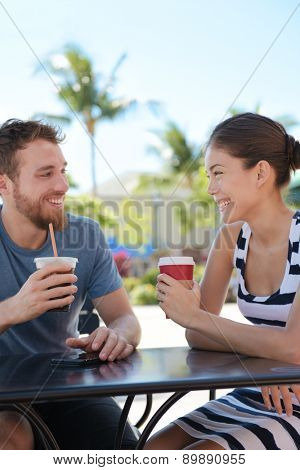 Cafe couple having fun drinking coffee talking smiling and laughing on date in summer. Young man talking with Asian woman sitting outdoors. Happy friends in late 20s.