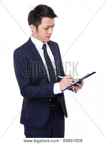 Businessman take note on clipboard