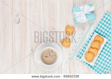 Coffee, heart shaped cookies and gift box on white wooden table with copy space