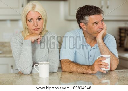 Mature couple having coffee together not talking at home in the kitchen