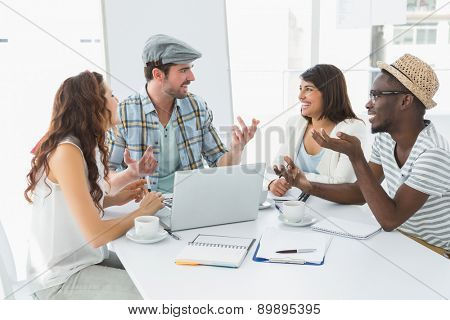 Smiling colleagues interacting and using laptop in the office