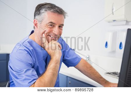 Portrait of a smiling dentist using computer in dental clinic