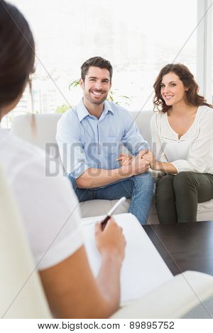 Reconciled couple smiling on couch in the therapist office
