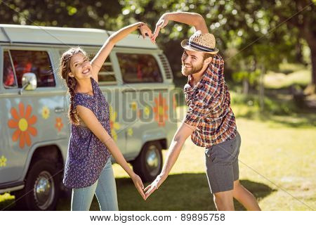 Hipster couple making heart with arms on a summers day