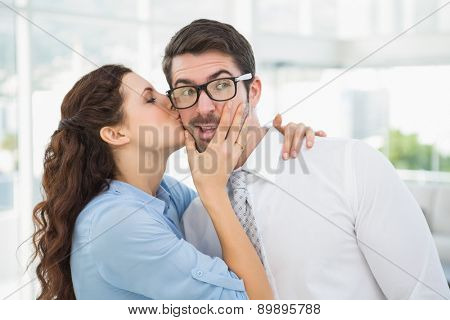 Businesswoman kissing her handsome colleague in the office