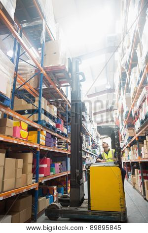 Focused driver operating forklift machine in warehouse