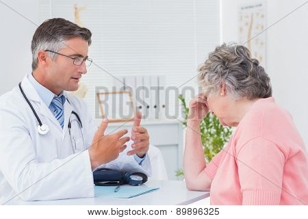 Male doctor talking to tensed female patient in clinic