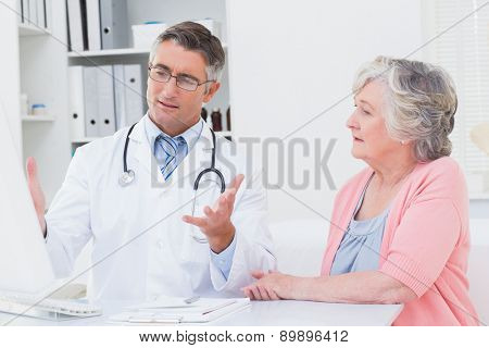 Male doctor explaning reports to senior patient on computer in clinic