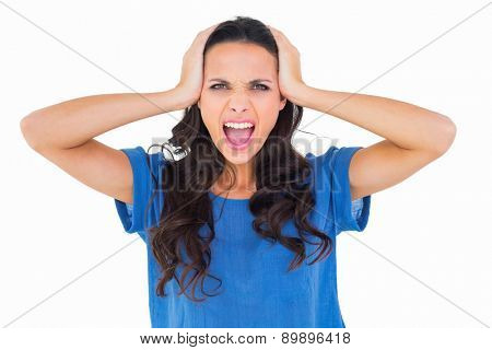 Angry brunette shouting at camera on white background