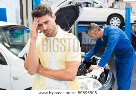 Customer feeling worried about his car at the repair garage