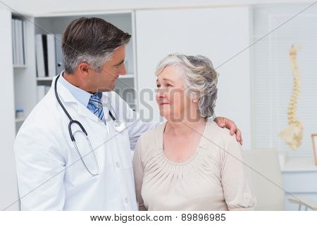 Male orthopedic doctor consoling senior woman in clinic