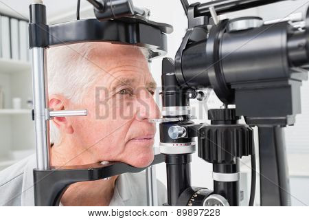 Senior man looking into slit lamp at clinic