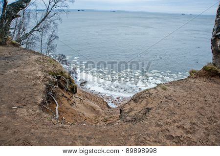 Cloudy,dark Silhouettes Of Trees With Green Leaves On The Hill, Blue Sea With White Small Ice Cubes