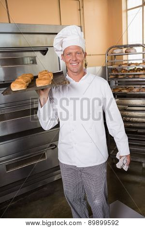 Baker holding tray of fresh bread in the kitchen of the bakery