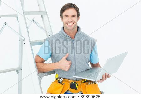 Portrait of repairman showing thumbs up sign while using laptop over white background