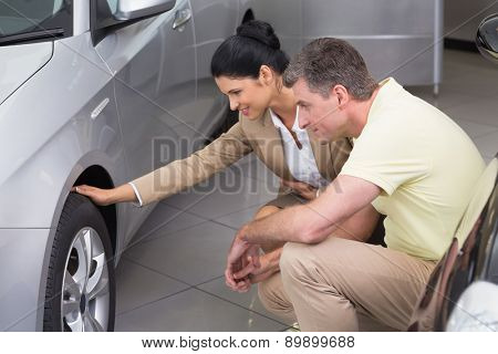 Businesswoman and customer discussing details of car tire at new car showroom