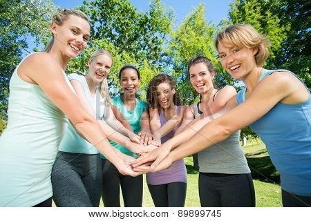 Fitness group putting hands together on a sunny day