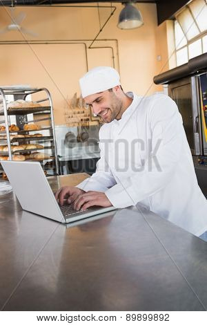 Smiling baker using laptop on worktop in the kitchen of the bakery
