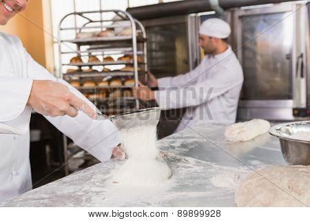 Smiling baker sieving flour on the dough in the kitchen of the bakery