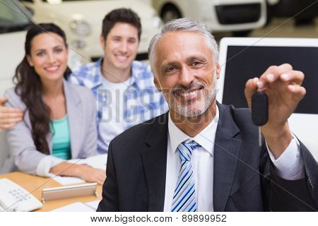 Smiling businessman showing a car key at new car showroom