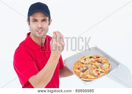 Portrait of handsome delivery man gesturing while holding fresh pizza on white background